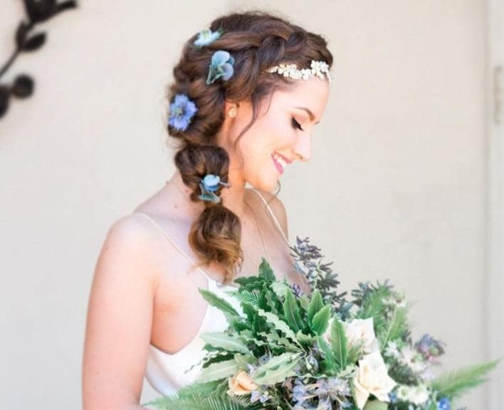 Curly wedding hair: Bride with side braided hairstyle in her long brown hair with flowers attached to it