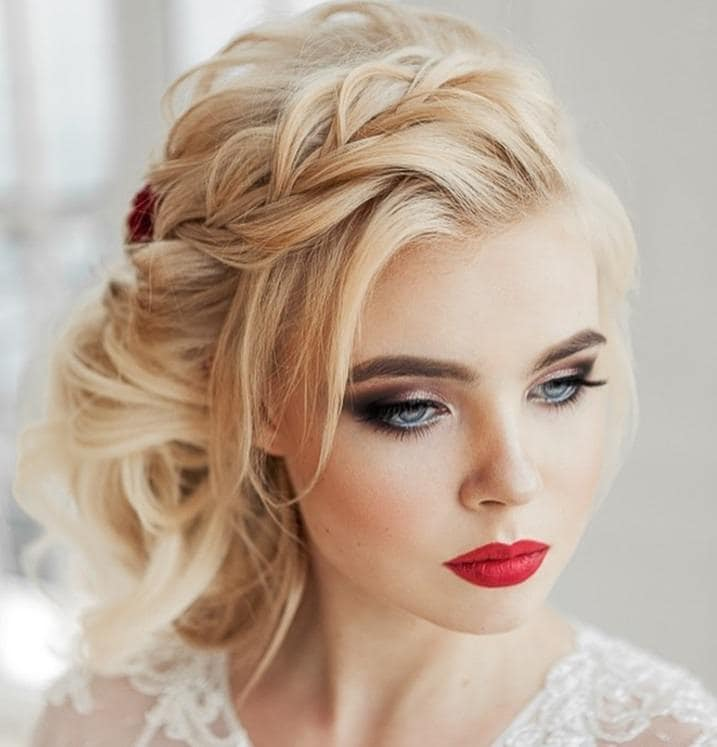 Curly wedding hair: Woman with blonde hair in a curly wedding hair styled into a side braided bun