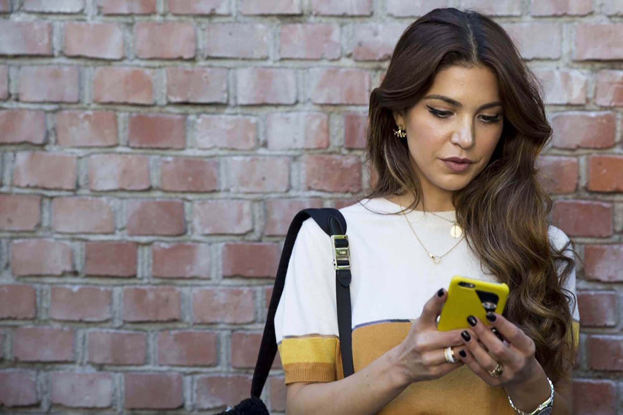 natural wavy hair: close up shot of woman with side swept dark brown waves, wearing white and gold top, posing against a brick wall and holding a phone
