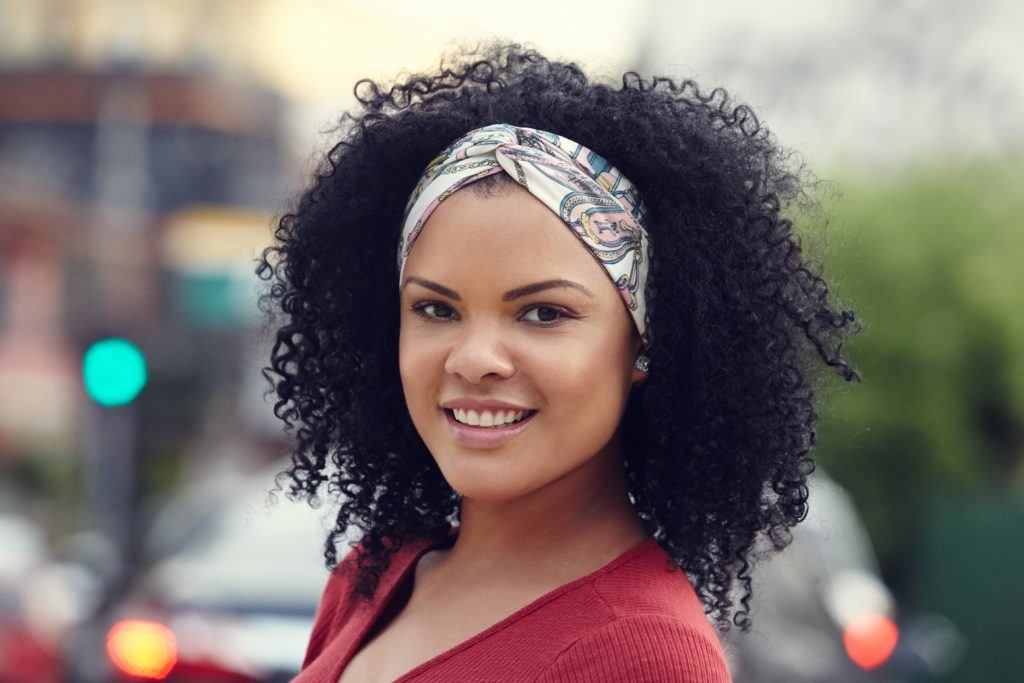woman with naturally curly brown hair wearing a silk scarf in a twisted headband wearing a pink red top
