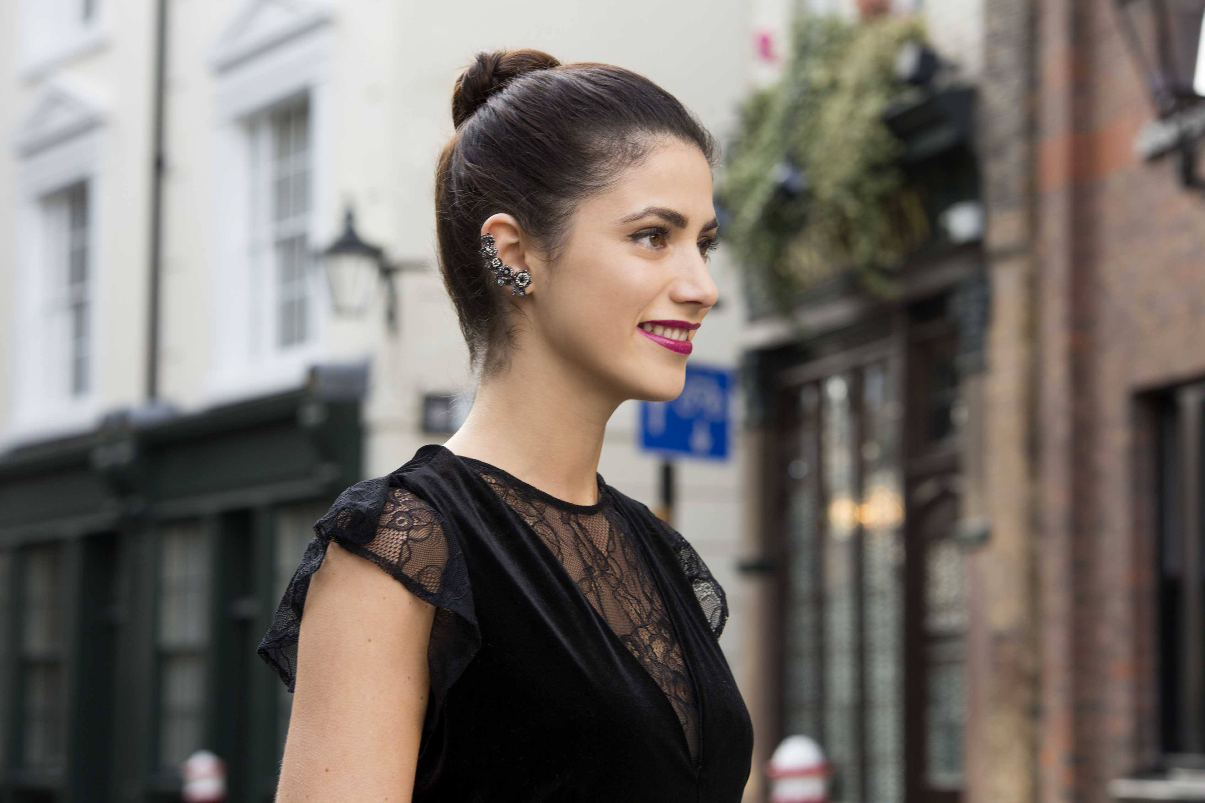 Christmas hairstyles: Woman with brown straight hair styled in a sleek top knot bun wearing a black lace top and red lipstick.