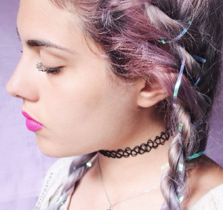 side view image of a woman with pink braided hair with tinsel intertwined in the hair