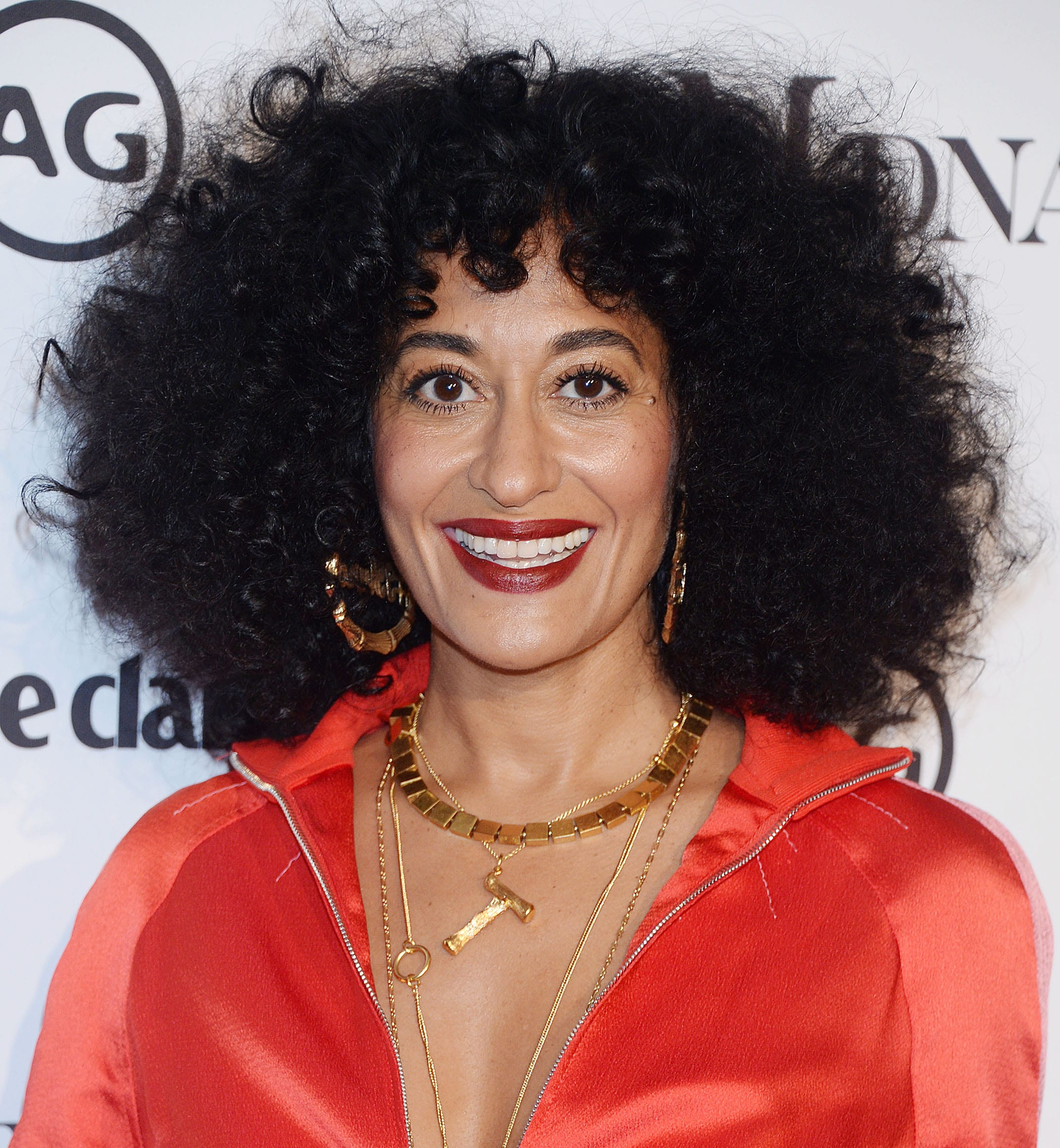 Curly hair hairstyles: Tracee Ellis Ross with dark brown shoulder length naturally curly hair with short micro fringe wearing red satin dress on red carpet