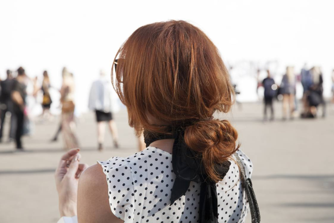 natural wavy hair: close up shot of the back of a model with a low, undone bun hairstyle, wearing polka dot top and posing on the street