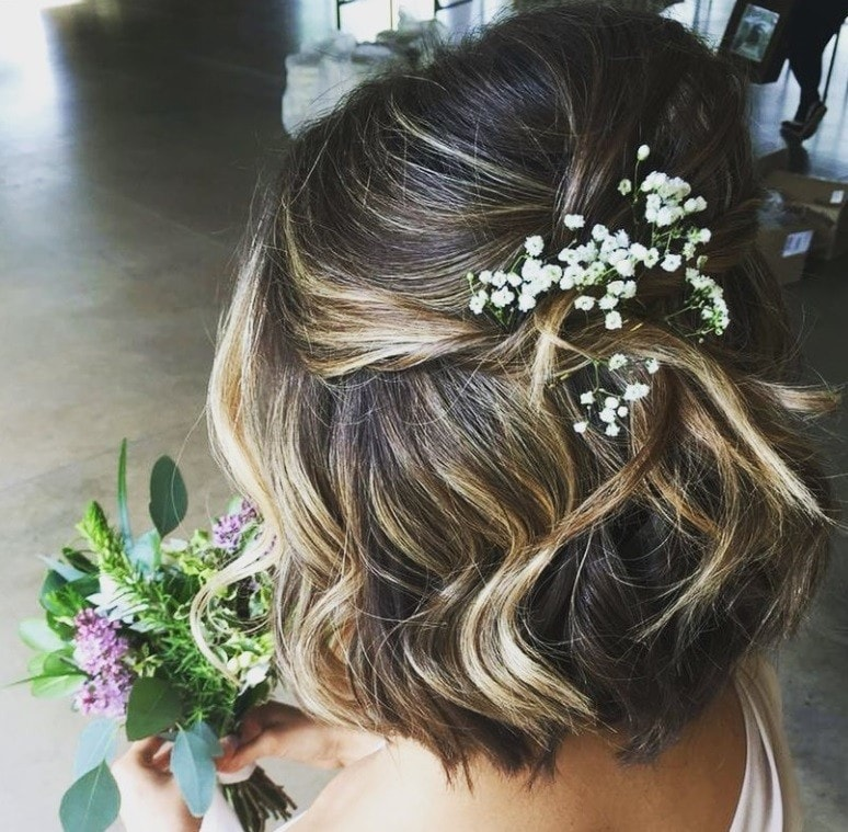 Curly wedding hair: Backshot of woman with brown hair with highlights in a half-up, half-down hairstyle with baby's breath flowers in it