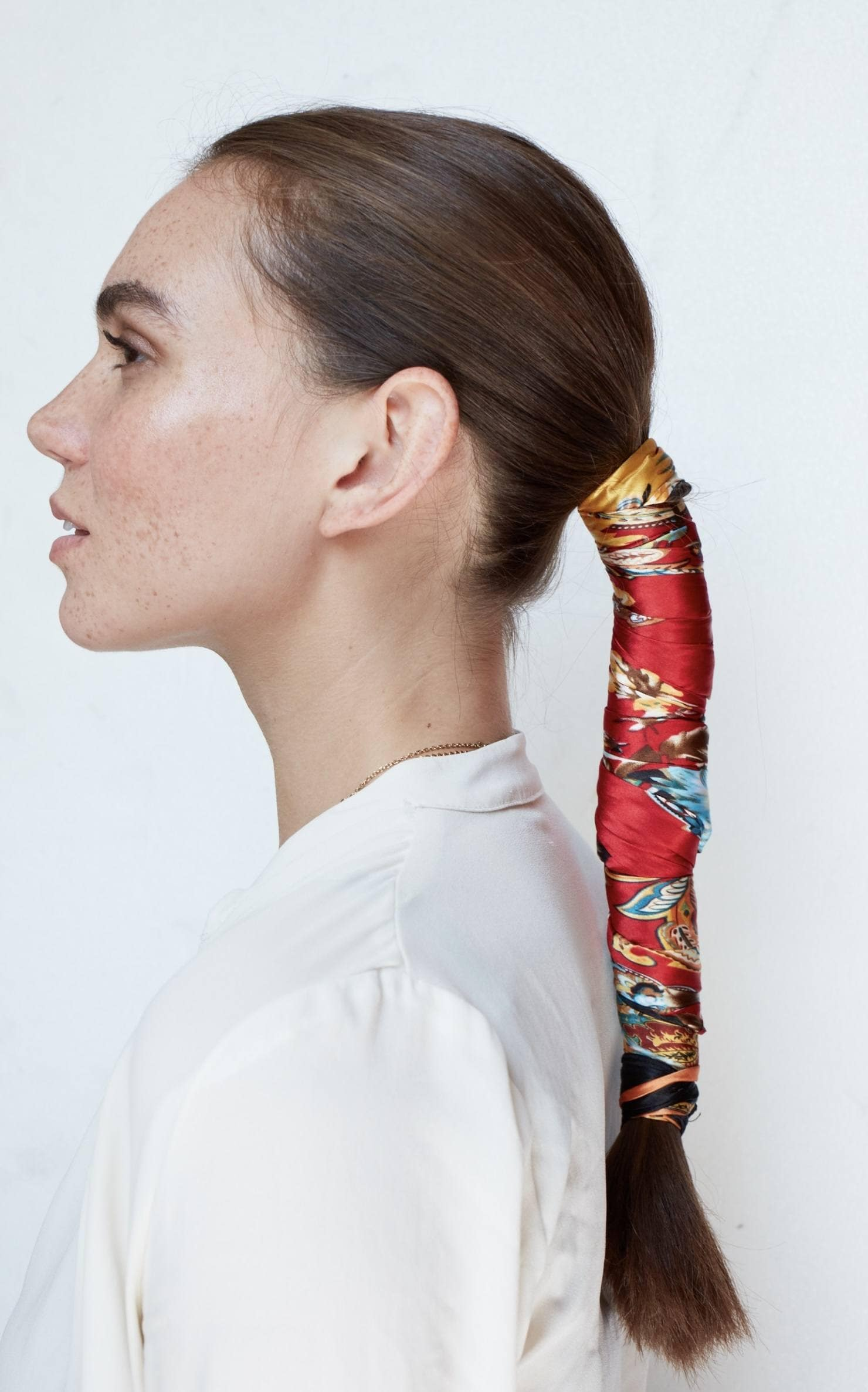 side profile shot of a brunette model with her hair in a low ponytail wrapped in a colourful red silk scarf