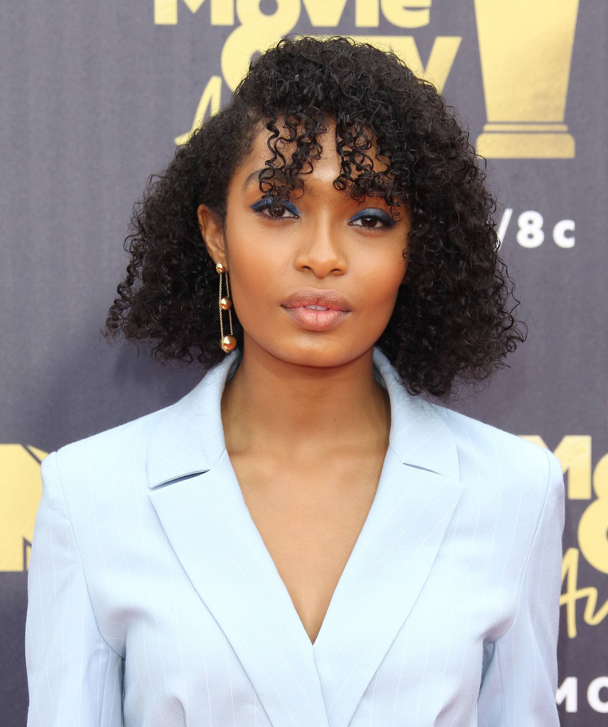 Curly hair hairstyles: Yara Shahidi with naturally curly bob length hair with curly side fringe wearing light blue suit on MTV red carpet