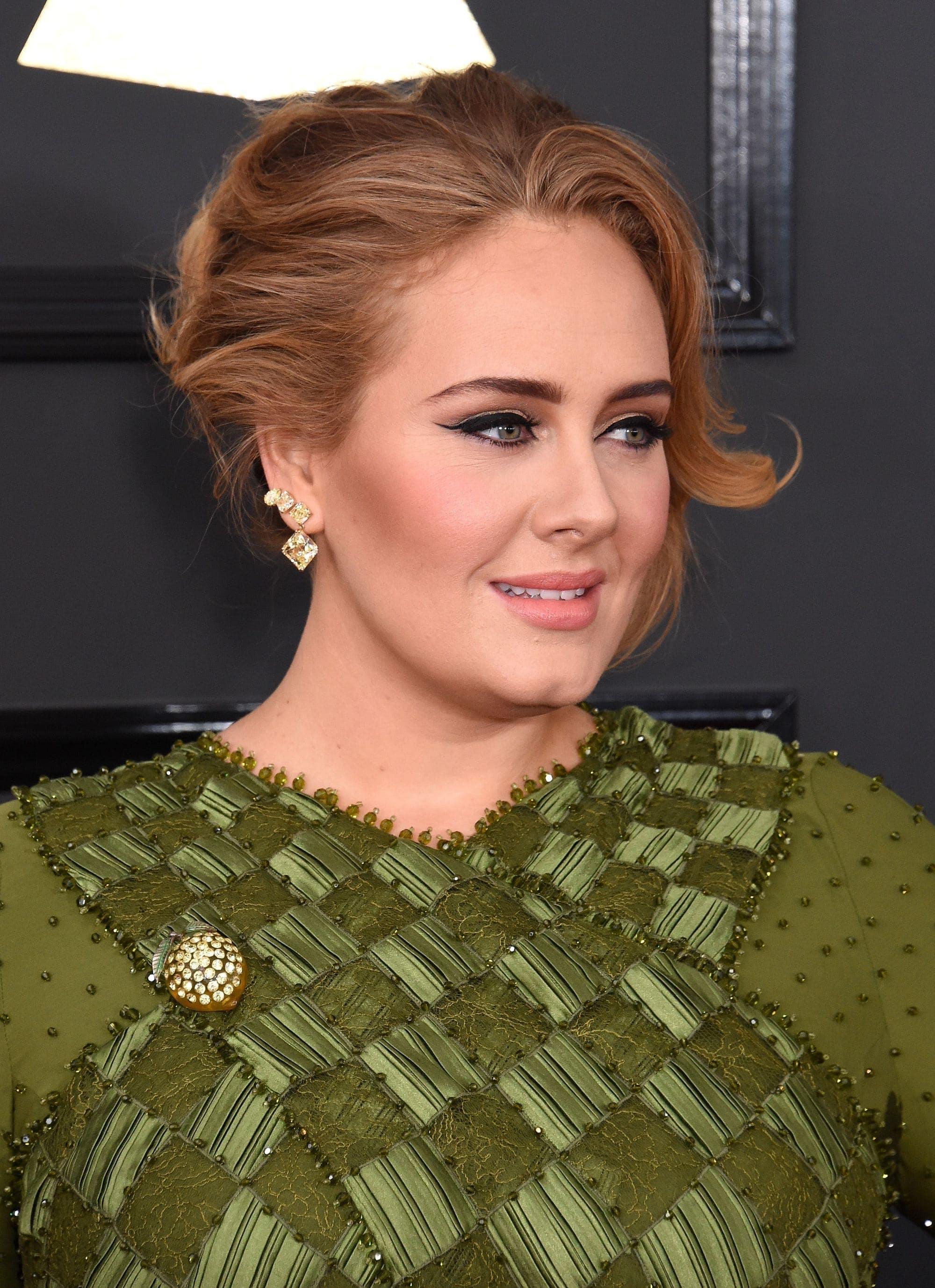 Red carpet hairstyles: Adele with light brown hair styled into a chic updo with loose tendrils
