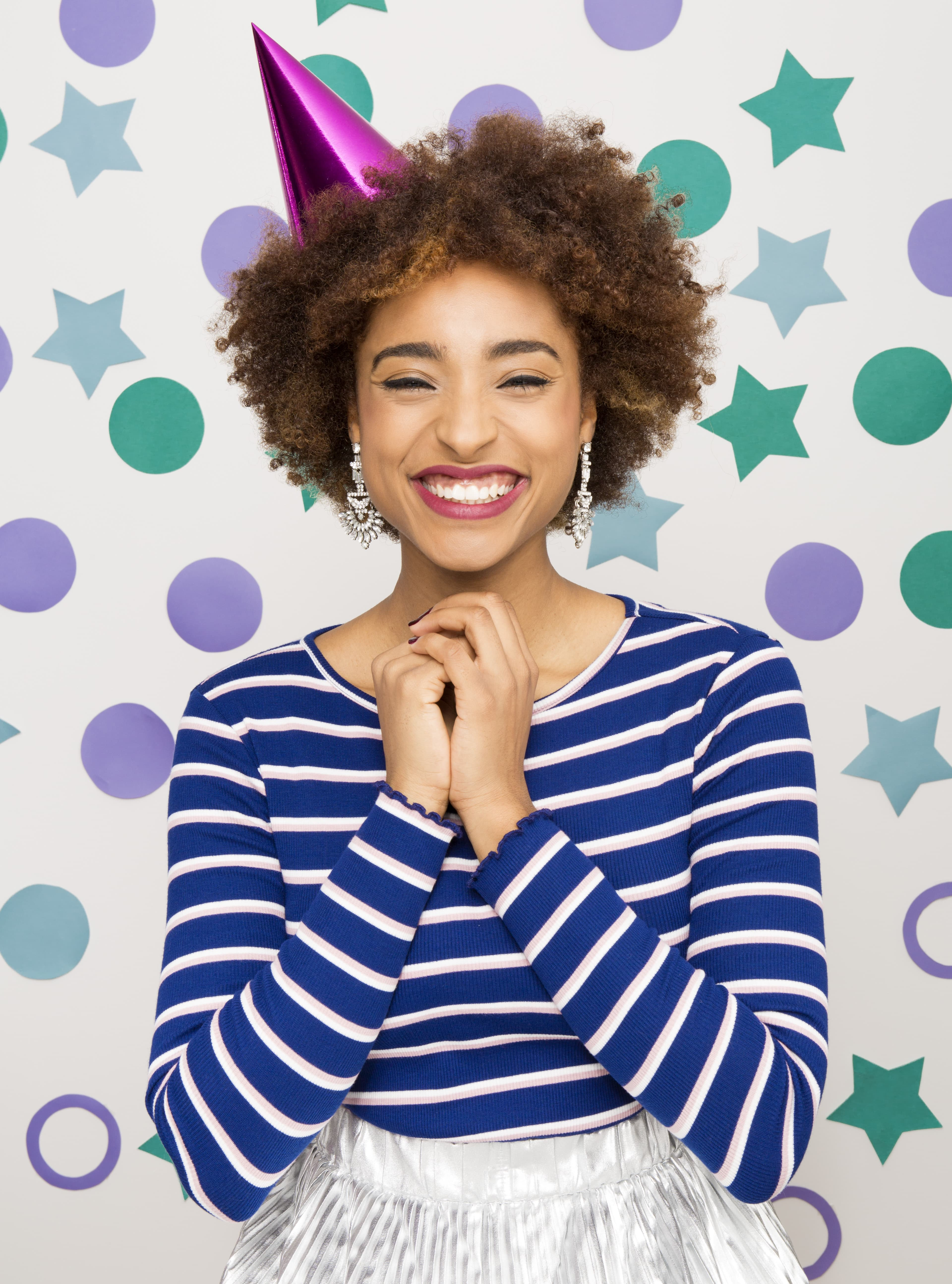 A young black model with a stripey blue and white top with a TWA and party hair