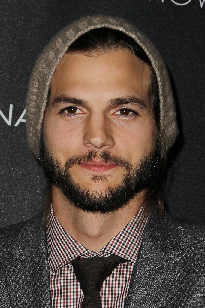 Ashton Kutcher on the red carpet wearing a grey suit and tie with a beanie hat on and neat facial hair