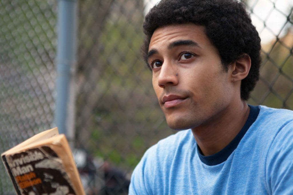 man playing the character of Barack Obama in the Barry Netflix's film with a small afro hairstyle wearing a blue t-shirt