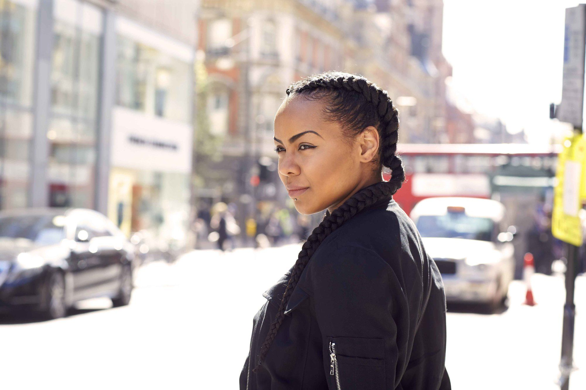 Winter hairstyles for natural hair: Side view of a woman with dark brown double boxer braids, wearing a black bomber jacket and standing in the street