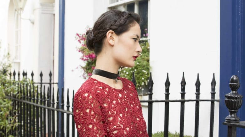 brunette model with a braided bun hairstyle wearing a red top and a black choker necklace
