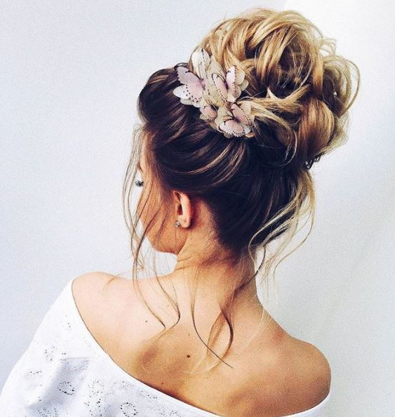 back side view of long blonde hair in high bun with butterfly hair accessories