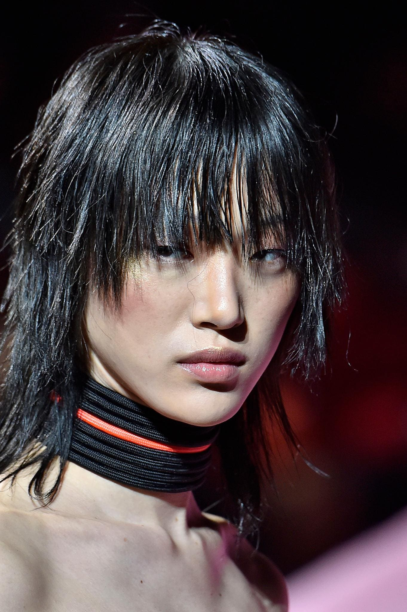 Retro hairstyles: Close up shot of a woman with a medium choppy shag haircut, wearing a choker on the Fenty Puma runway
