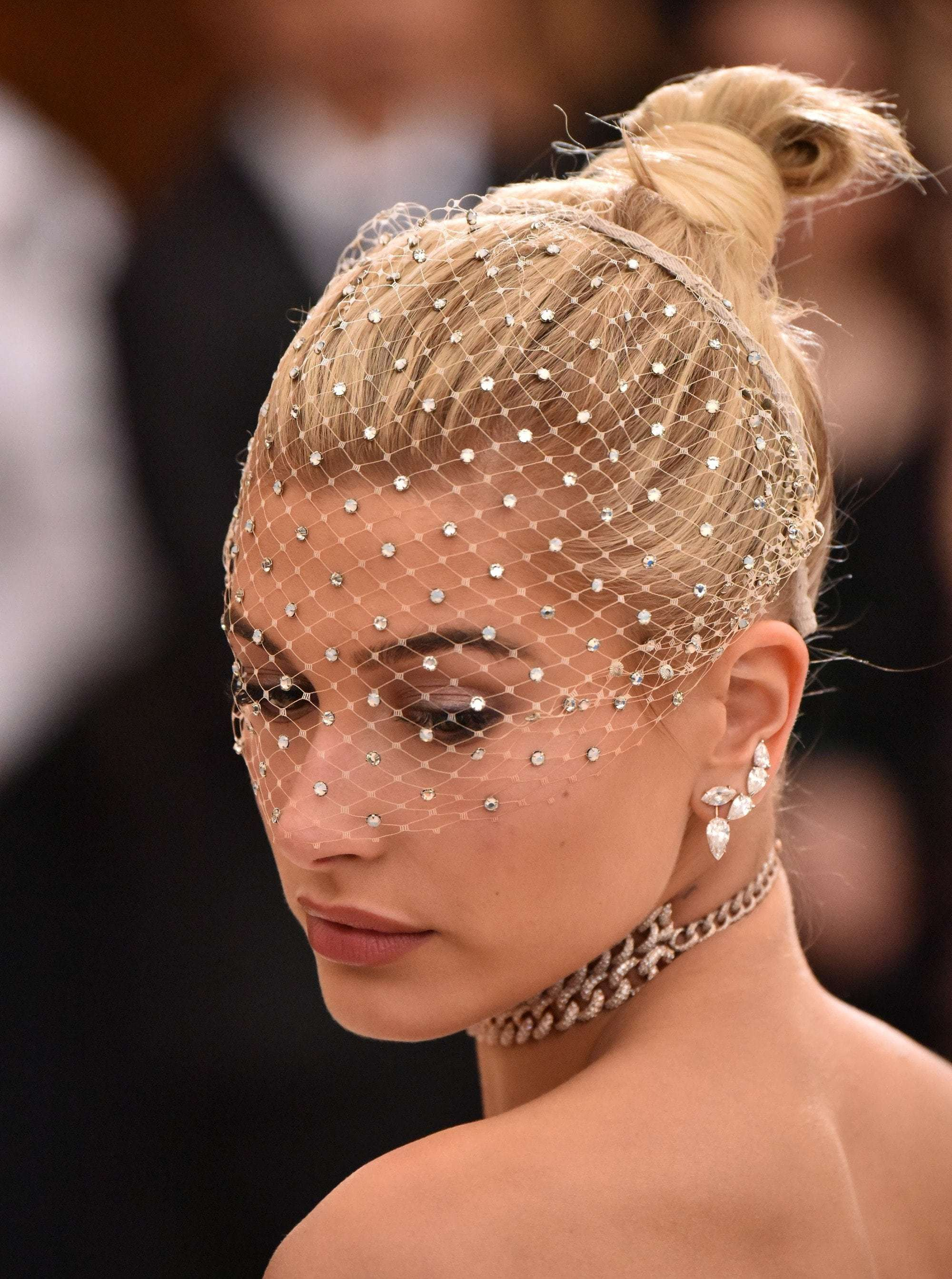 Red carpet hairstyles: Hailey Baldwin with blonde hair styled into a updo with pearl net veil