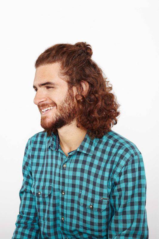 half up top knot on man with curly brown hair