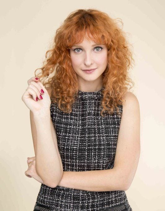 girl posing with red curly hair with a fringe