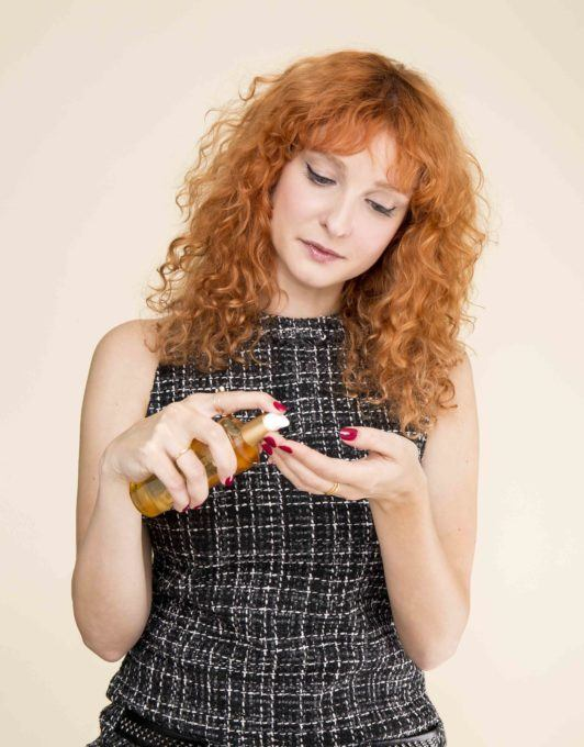 girl with red curly hair applying serum