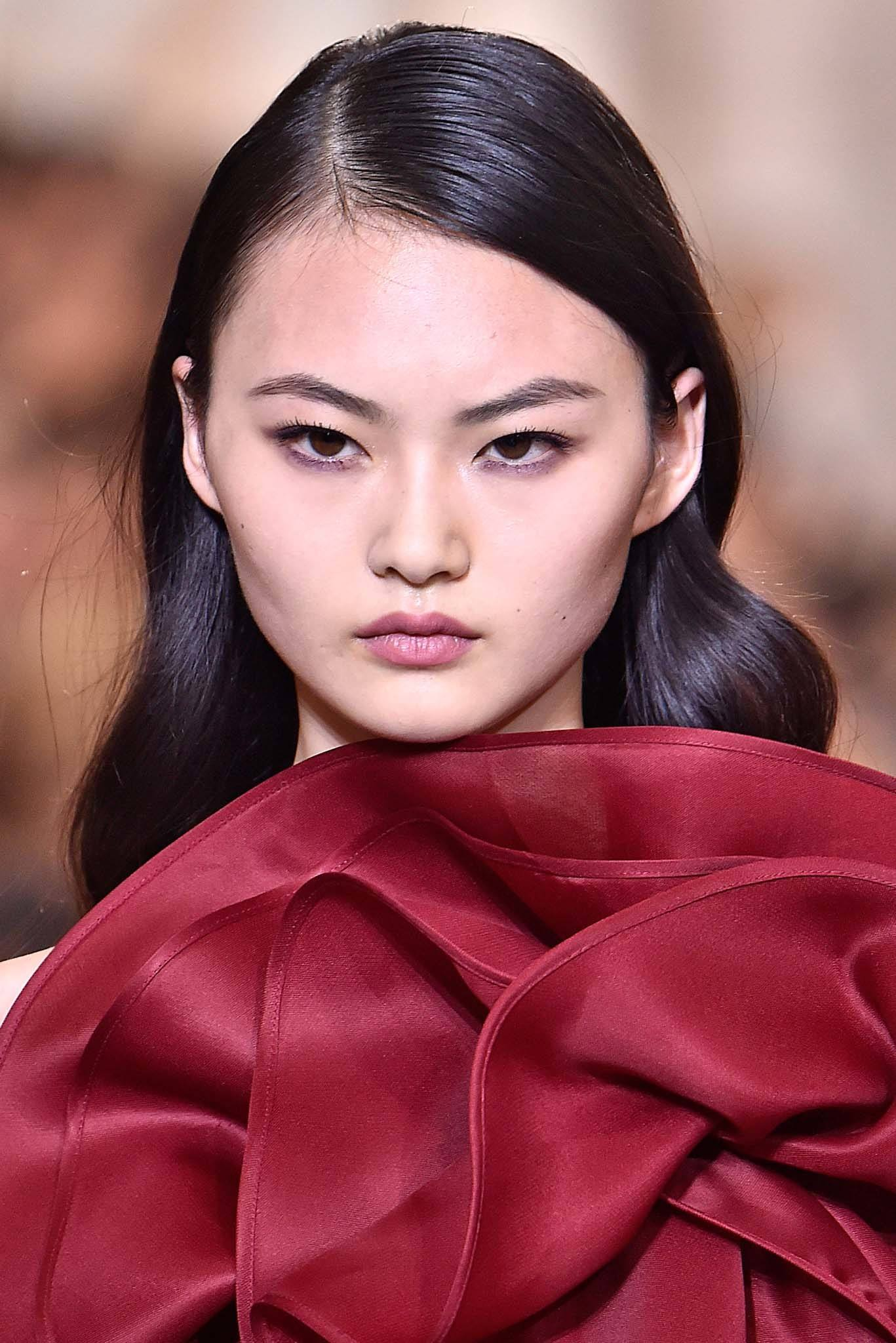 Retro hairstyles: Close up shot of a model with dark brown long hair styled into Hollywood waves, wearing red and walking on the Elie Saab runway