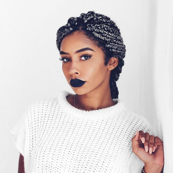 Winter hairstyles for natural hair: Image of a woman with grey box braids worn in a low ponytail, wearing a short sleeve white knitted jumper