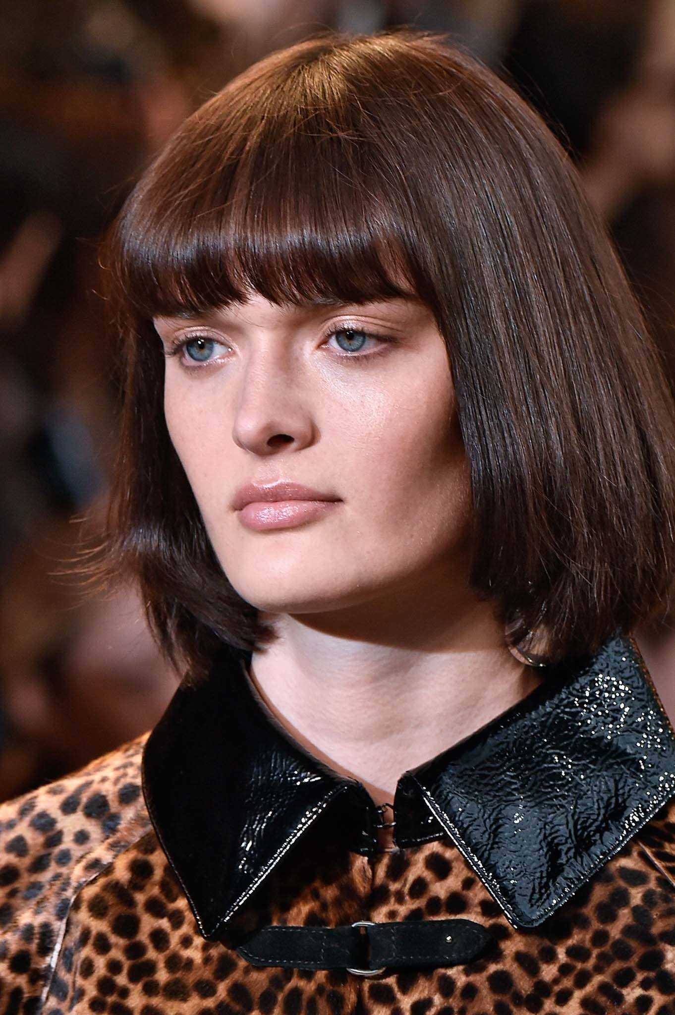 Retro hairstyles: Close up shot of a model with chestnut brown bob with bangs on the Isabel Marant runway