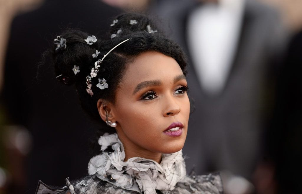 close up shot of janelle with space bun afro hairstyle that has accessories in it, wearing ruffled dress