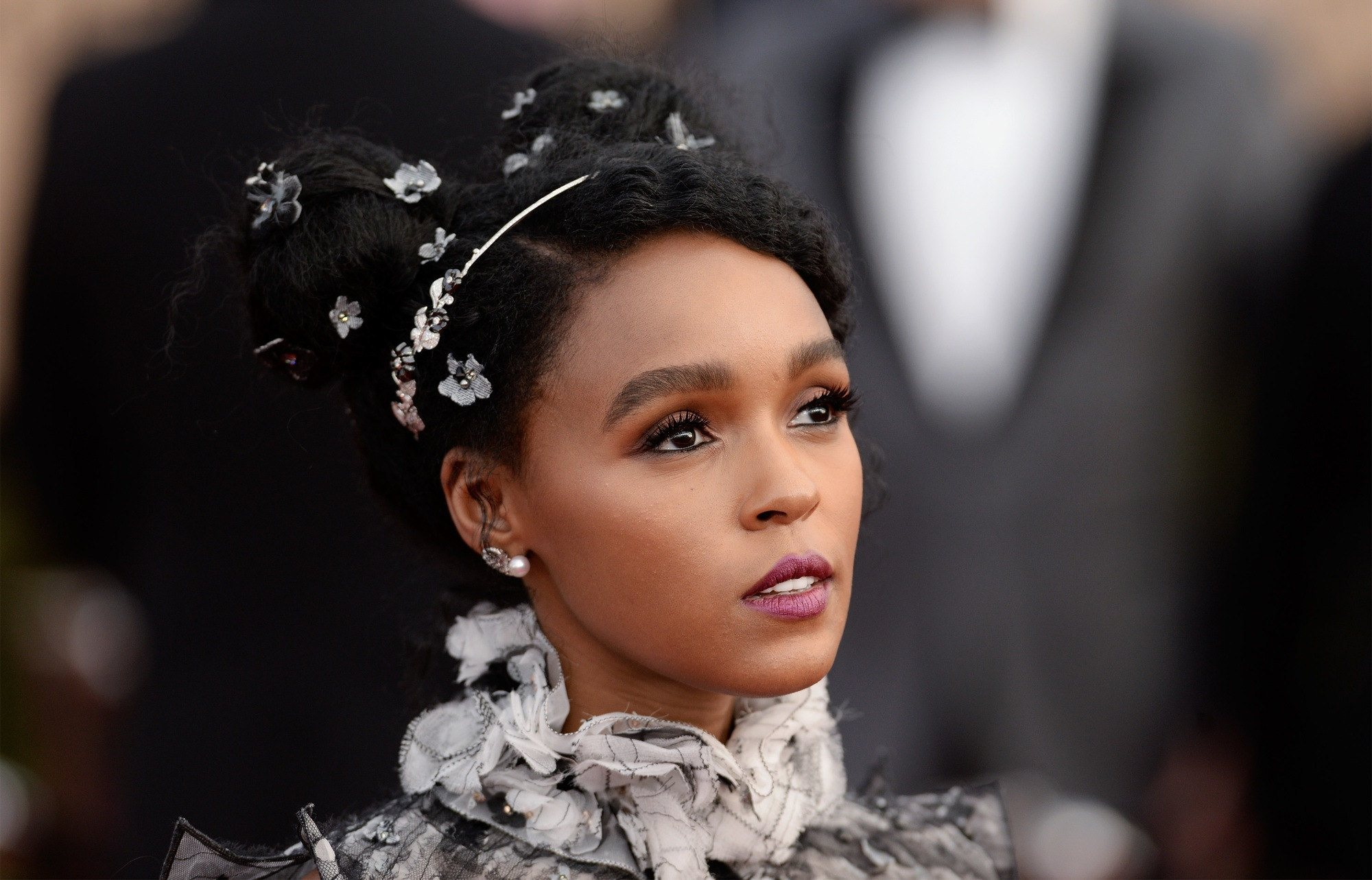 Red carpet hairstyles: Janelle Monae with a twin bun updo with floral accessories
