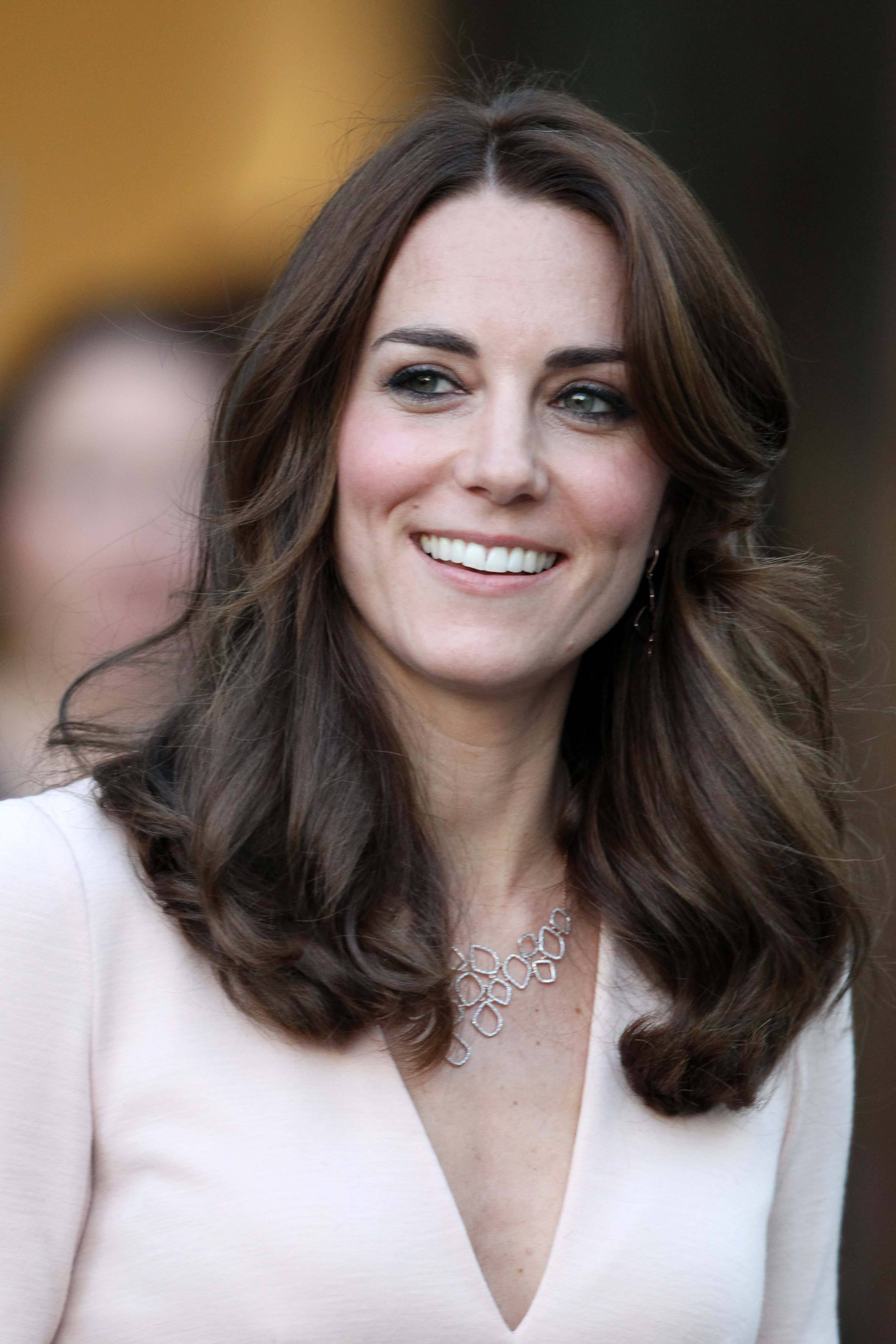 close up shot of kate middleton with brown blow out hairstyle, wearing nude pink dress and silver necklace