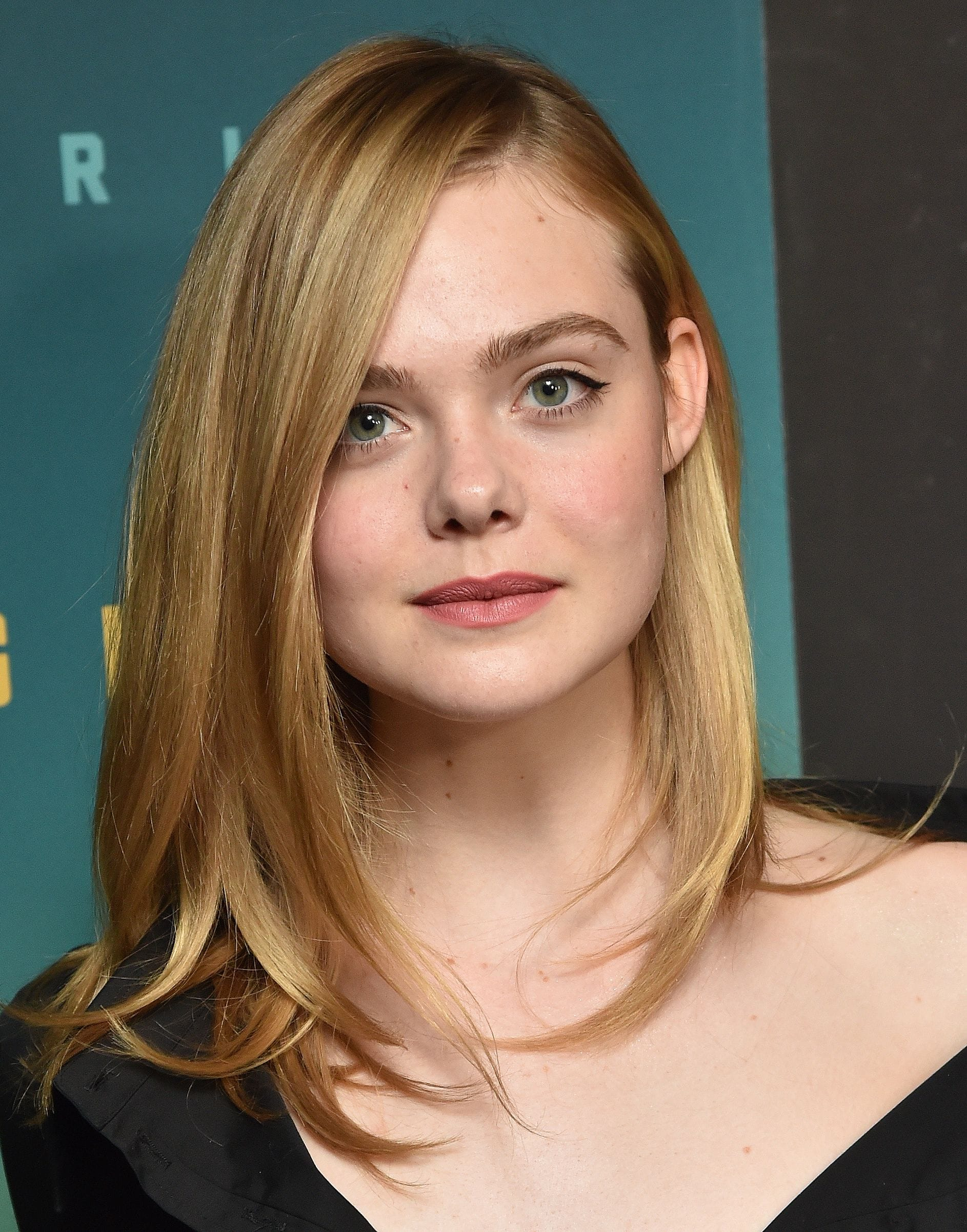Red carpet hairstyles: Elle Fanning with straight blonde shoulder length hair parted down the side wearing a black dress.