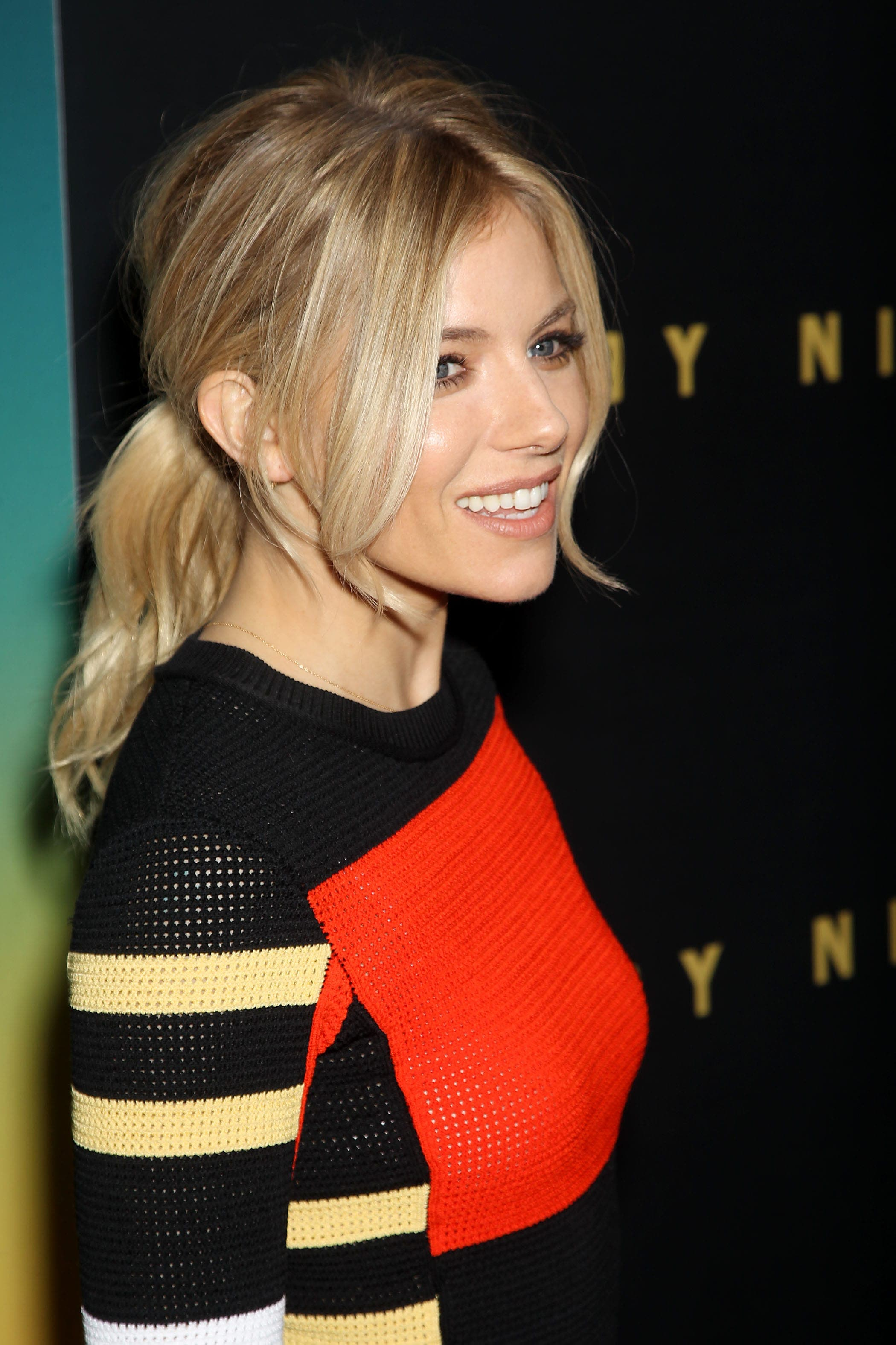 Red carpet hairstyles: Sienna Miller with straight blonde hair in low ponytail with loose long bangs wearing a striped jumper.