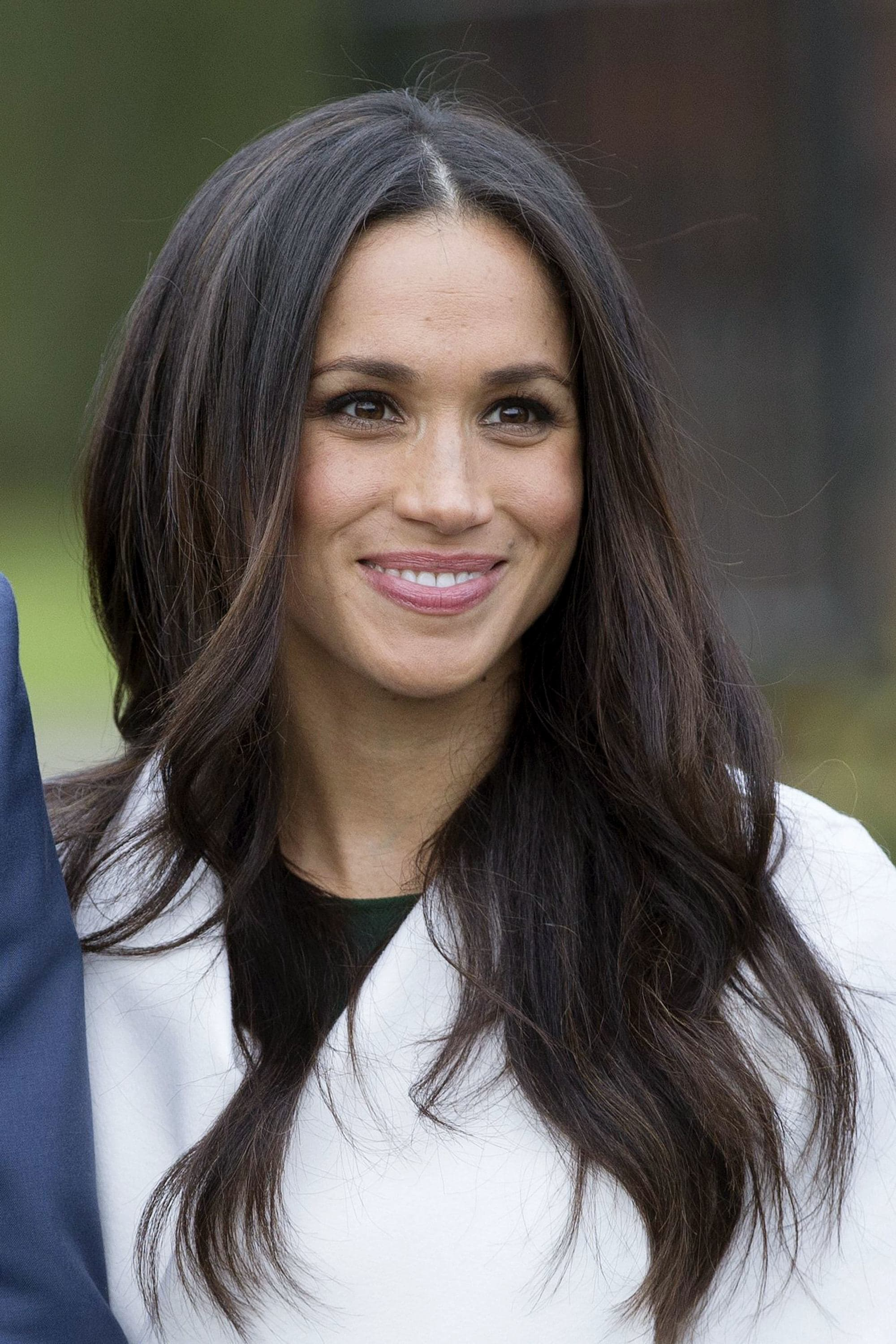 close up shot of meghan markle with blow out hairstyle, wearing white jacket, standing outside of kensington palace