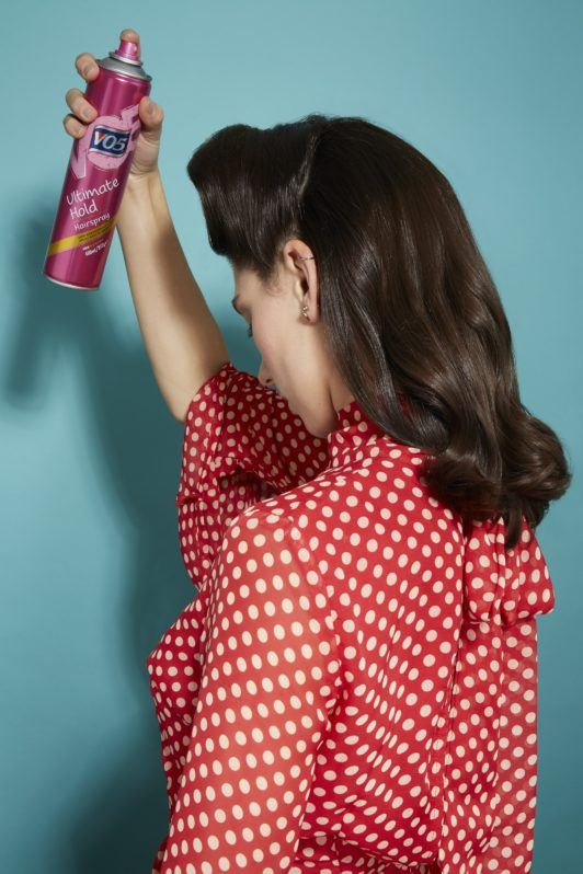 back view of a woman with dark brown glossy hair in loose curls and retro rolls spraying her hair with hairspray