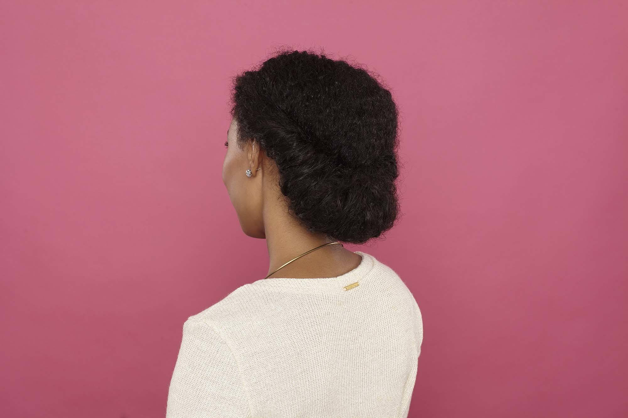 hairstyles for black women: close up shot of a woman with natural, chocolate brown hair styled into a low rolled updo, wearing white and posing in a studio setting