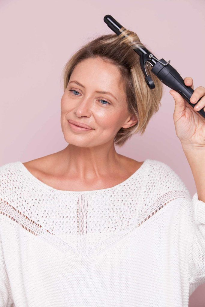 blonde-haired women shows us how to curl very short hair with a curling wand