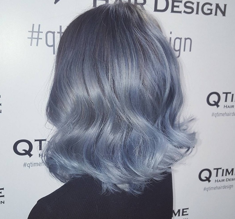 back view of woman with silver blue denim hair colour with slight wave pattern on shoulder length tresses