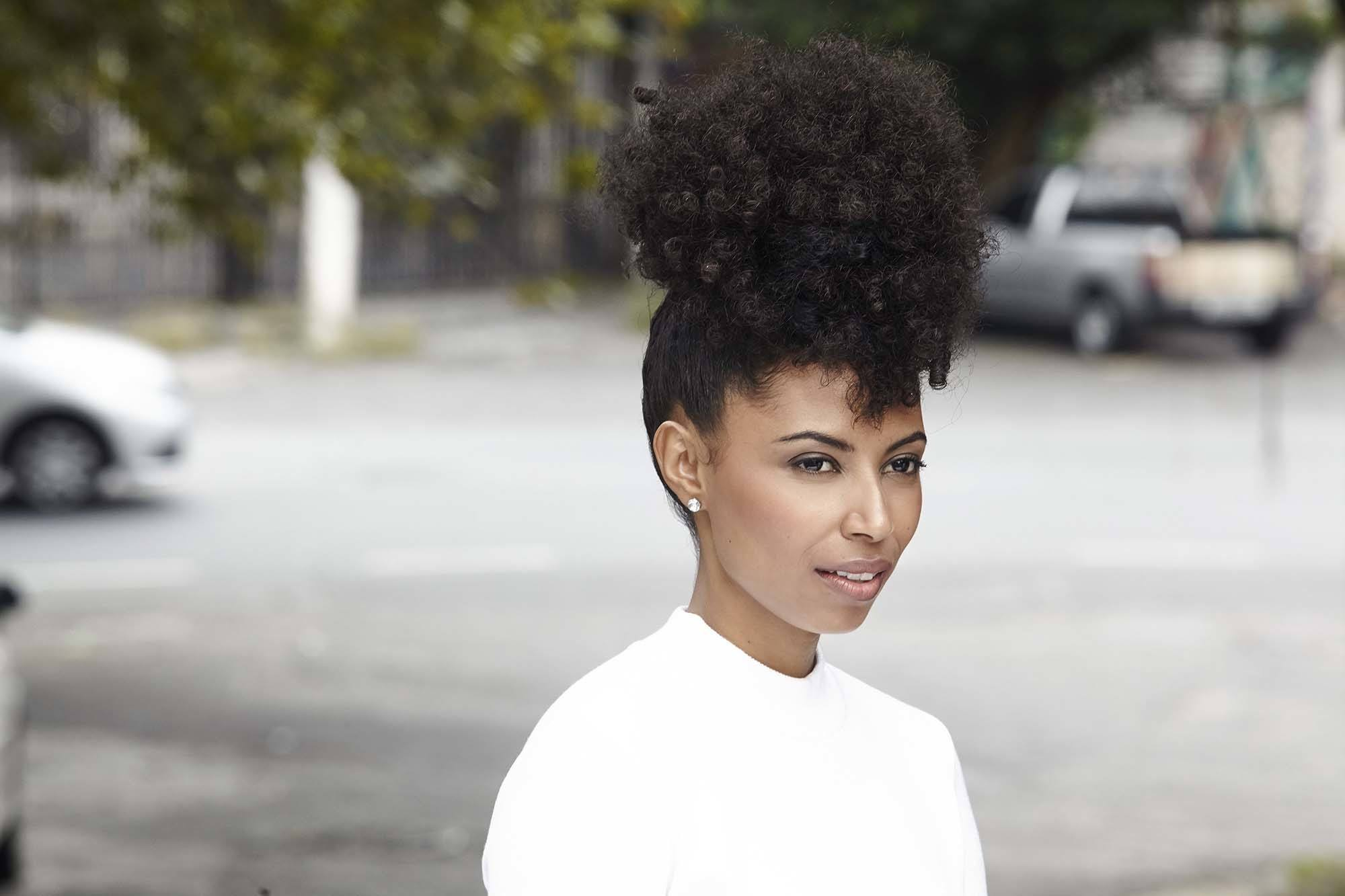 black hairstyles: close up shot of woman with natural chocolate brown hair styled into a pineapple updo, wearing white and posing on the street