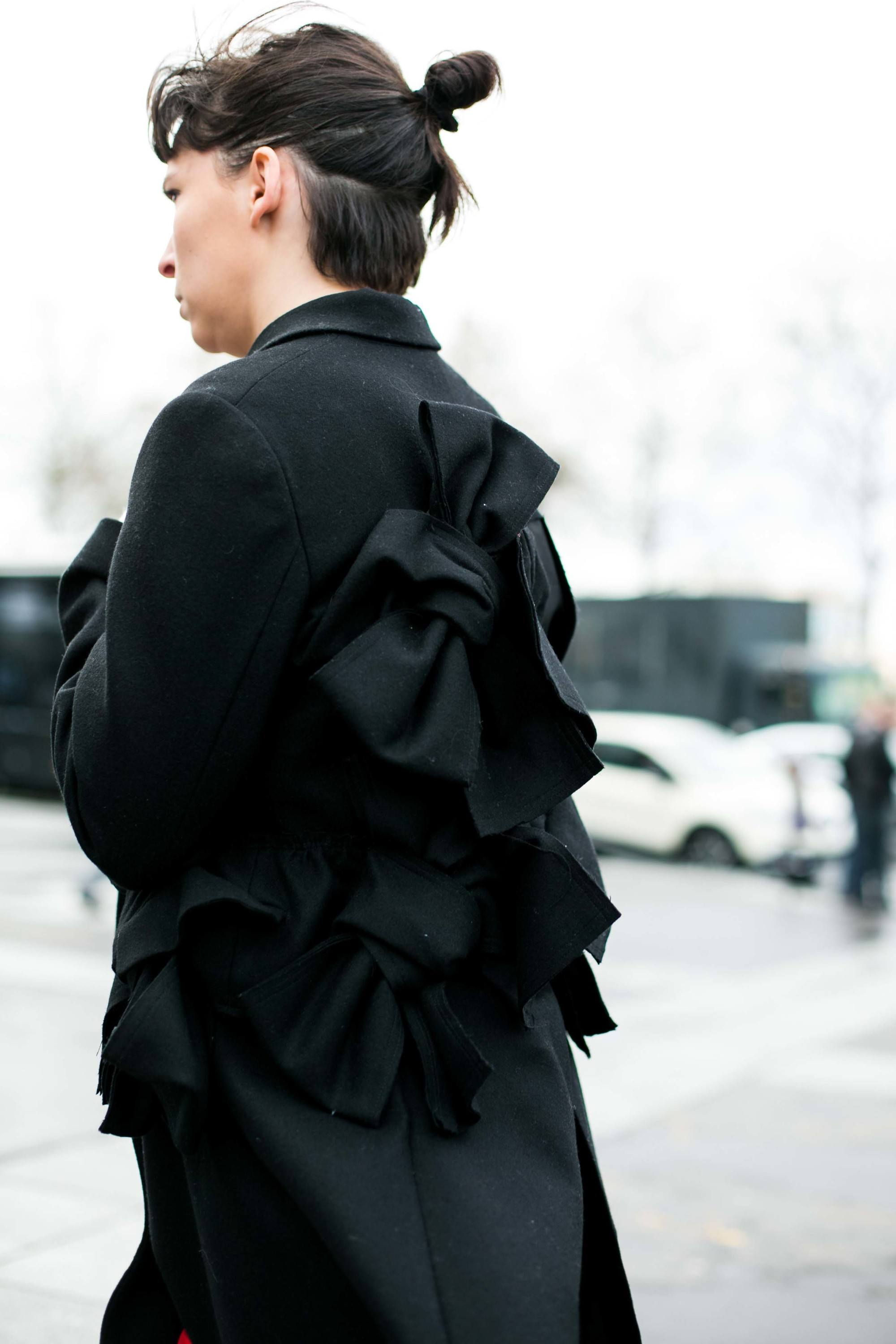 Gym hairstyles for short hair: Street style shot of the back of a brunette model with a half-up bun hairstyle, wearing all black