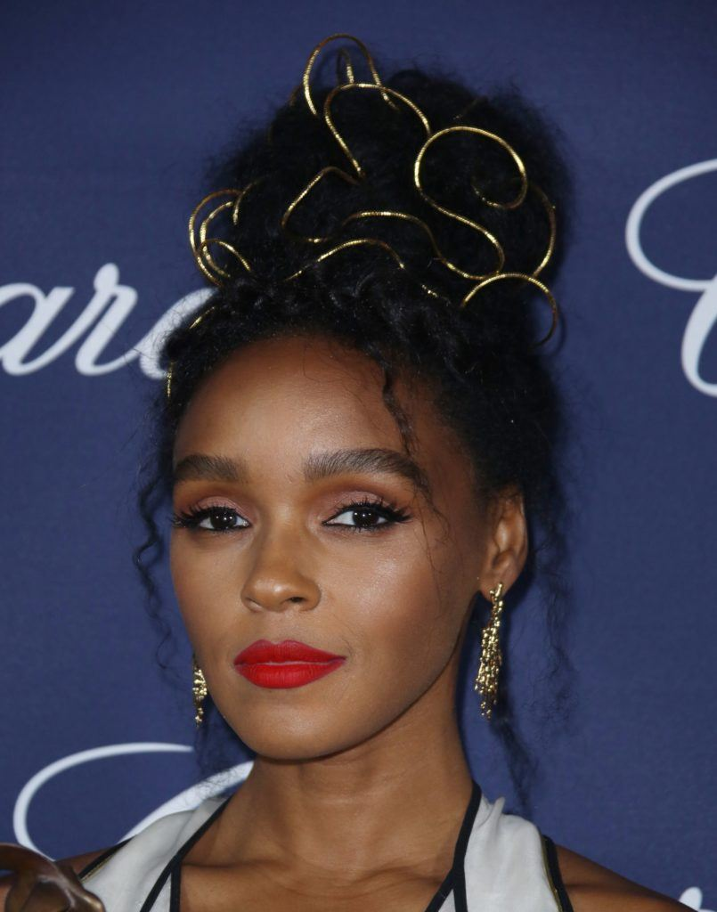 Janelle Monae wearing her hair in an updo on the red carpet with gold wiring pulled through