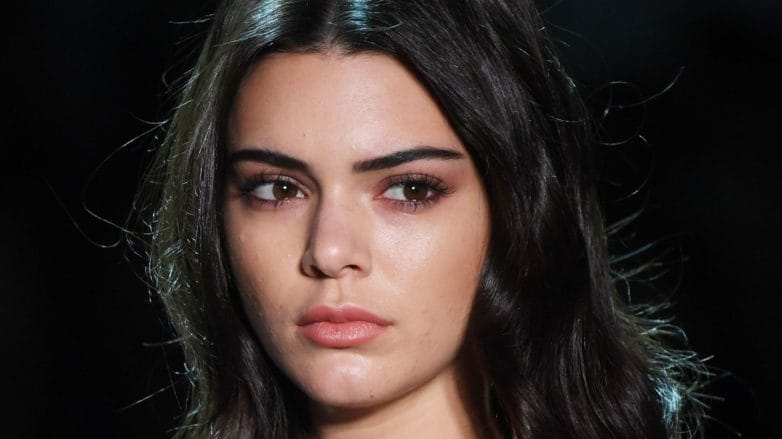 Kendall Jenner with dark shoulder length hair walking on the runway