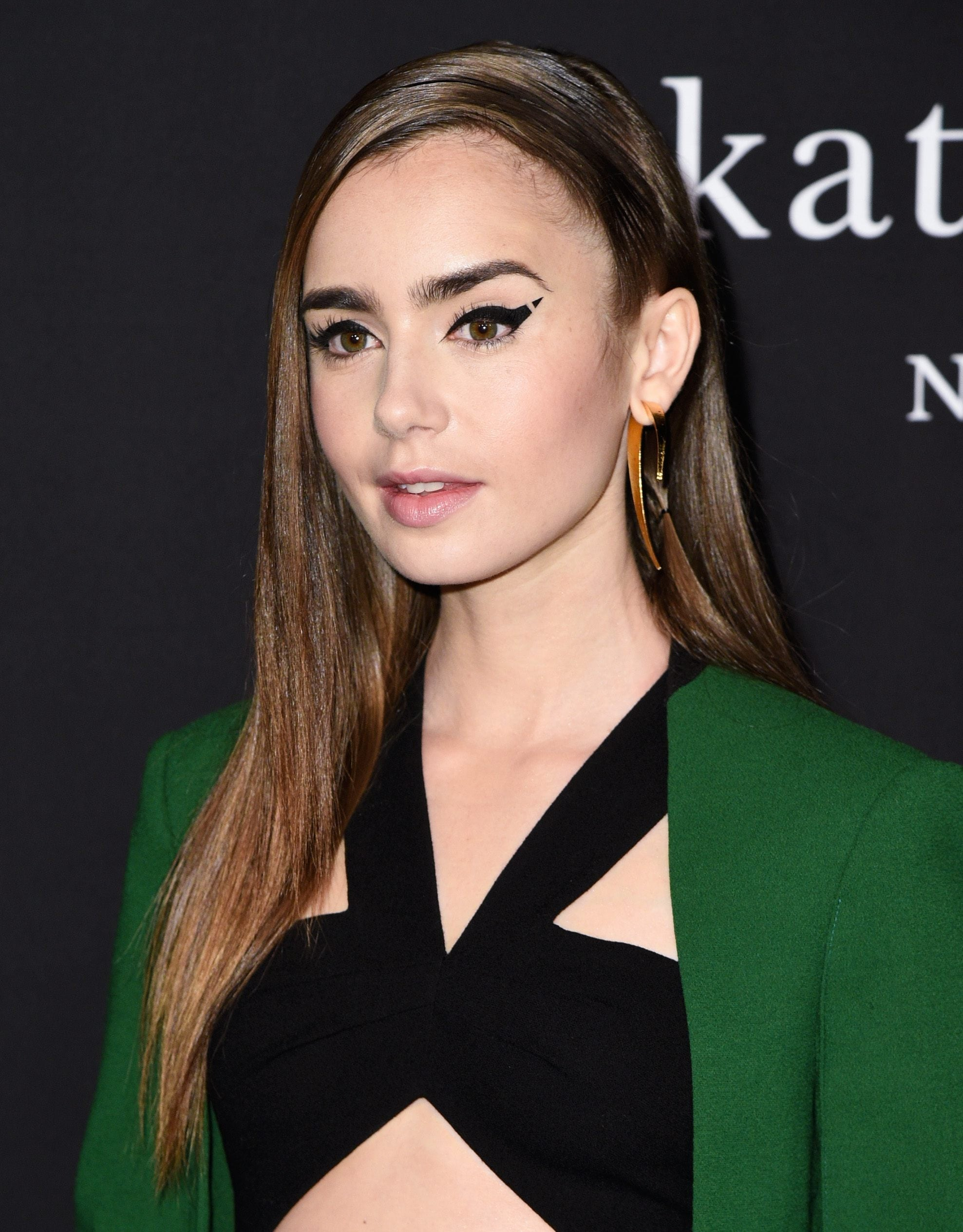 Side hairstyles: Lily Collins with long brunette hair swept over to one side with a deep set side parting, wearing a black cut out top and green blazer