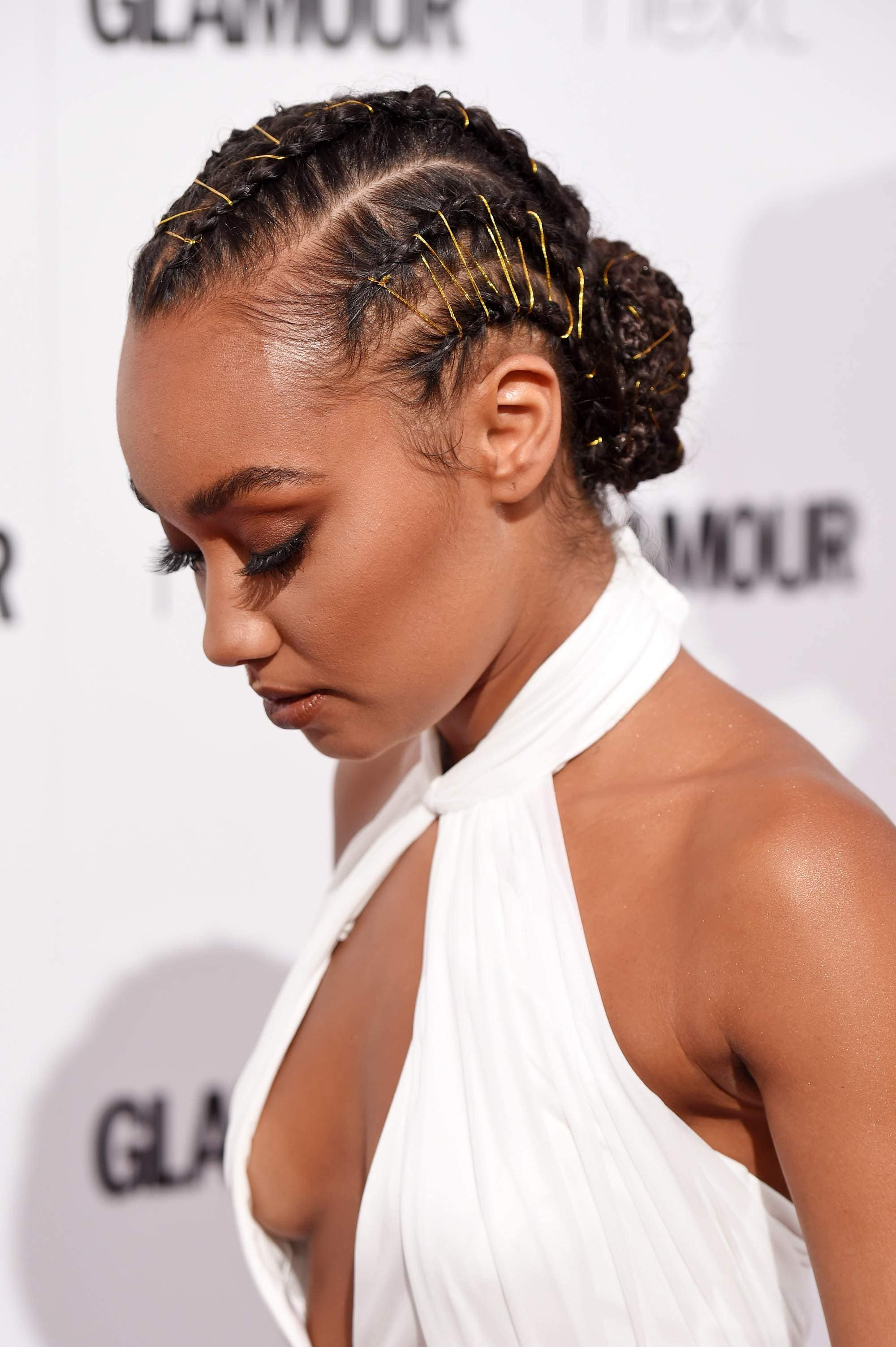 black hairstyles: close up shot of a little mix leigh anne pollack wearing a box braided bun, wearing a white keyhole dress, posing on the red carpet