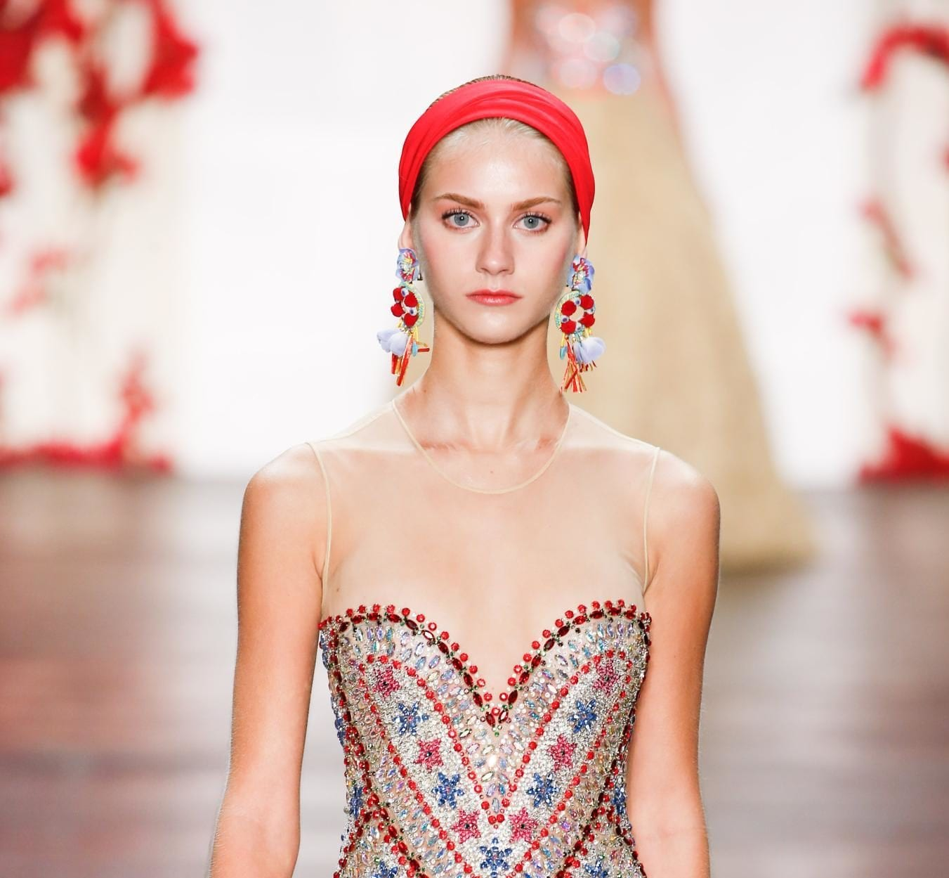 Gym hairstyles for short hair: Blonde model on runway with a red satin headband, wearing a strapless colourful dress