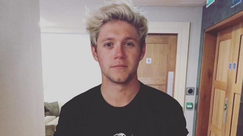 Niall Horan wearing a black tshirt with a logo on it with his blonde hair worn in a quiff with dark roots