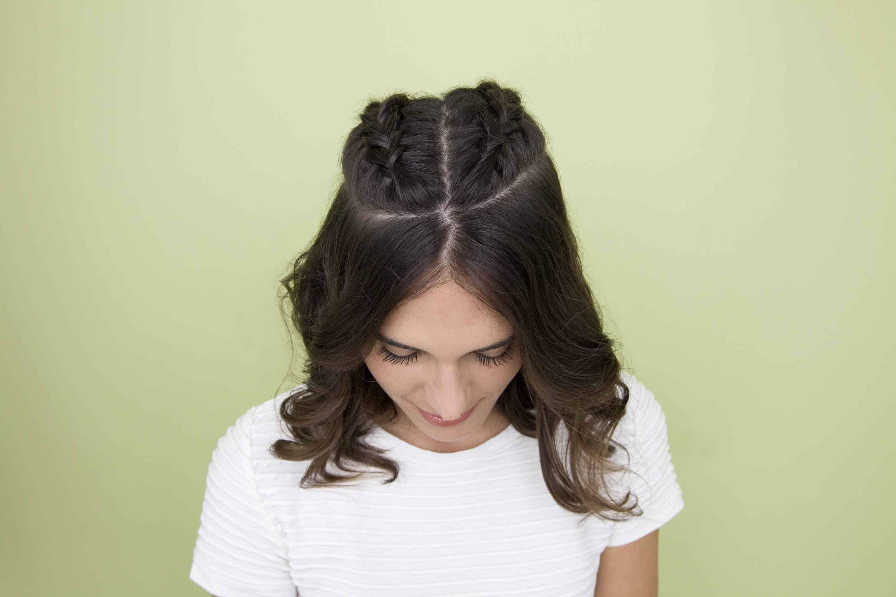 Gym hairstyles for short hair: Close-up shot from above of a brunette with curly mid-length hair styled in half-up half-down double Dutch braids, wearing a white t-shirt against a green background