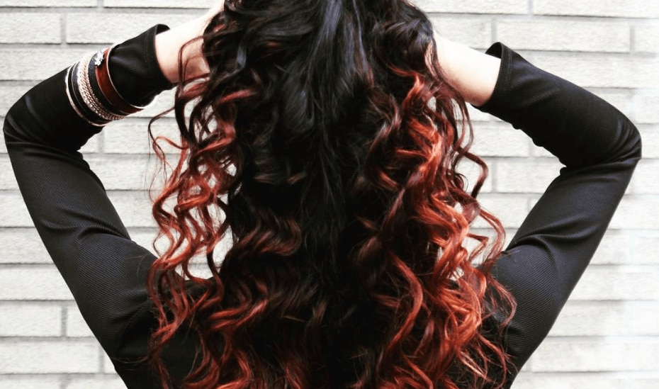 woman with ombre red curly hair wearing all black