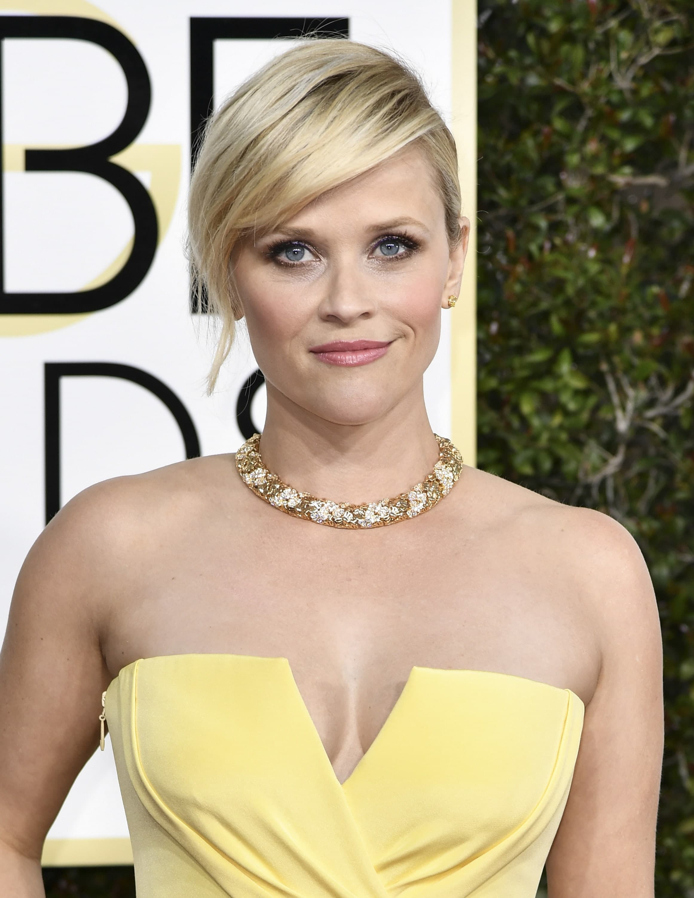 Reese Witherspoon with side fringe wearing yellow strapless dress