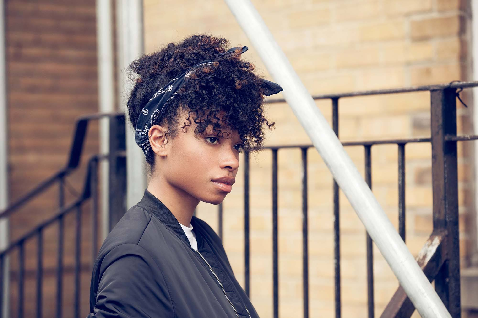 Gym hairstyles for short hair: Woman with curly natural hair in an updo tied with a hair scarf, wearing a bomber jacket and standing outside