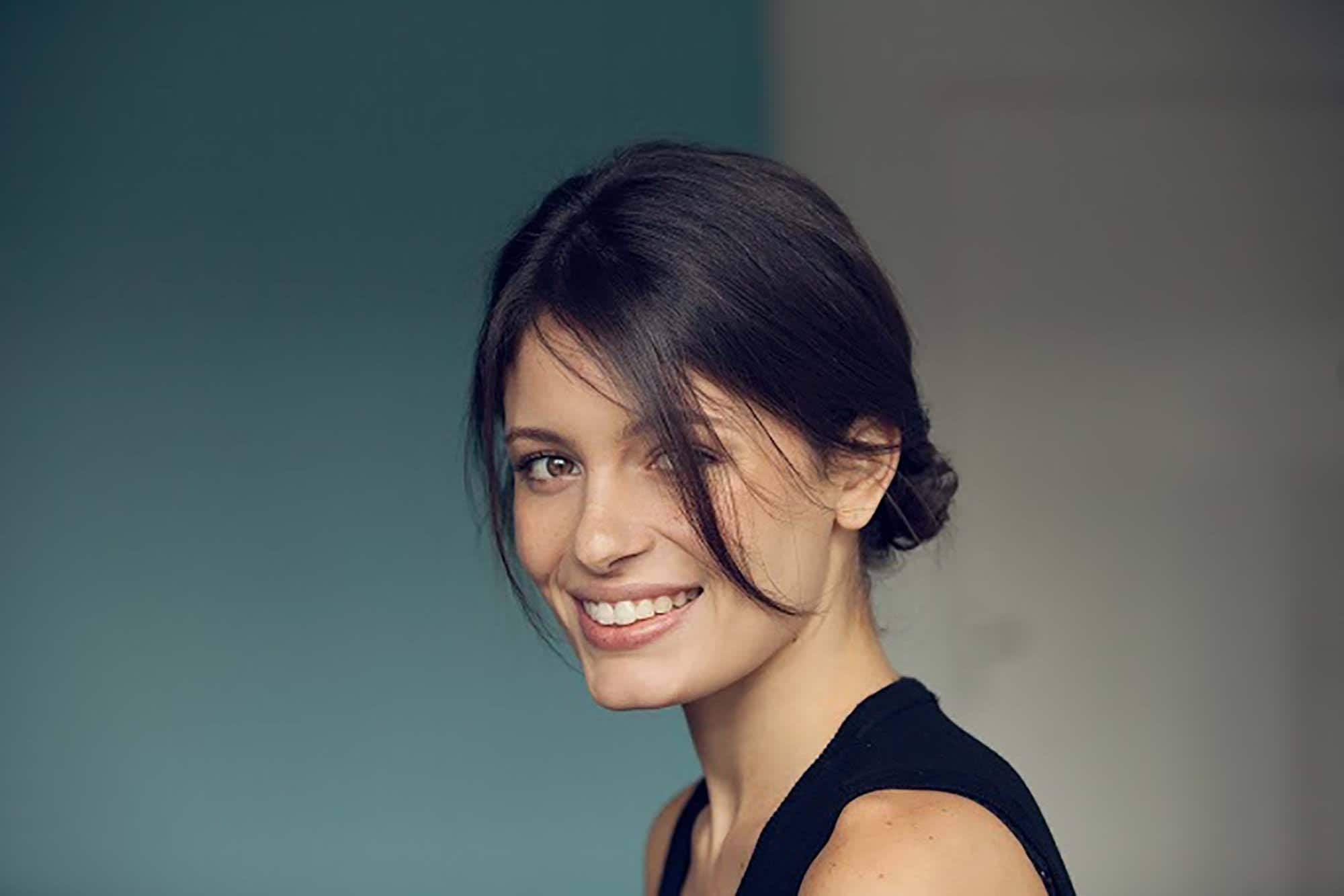 Gym hairstyles for short hair: Brunette woman with a low bun hairstyle