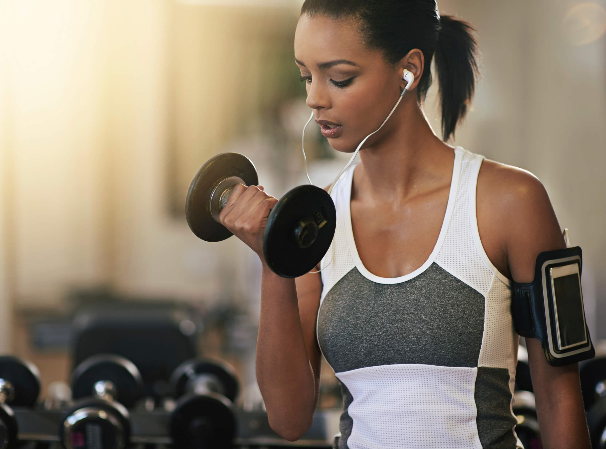 Gym hairstyles for short hair: Sporty brunette with a low ponytail, lifting dumbells in the gym